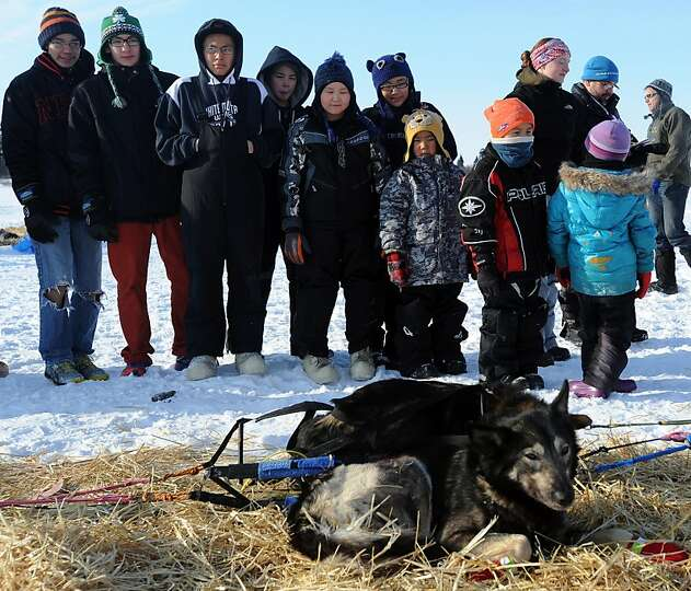 Children from White Mountain School look at Mitch Seavey's dogs resting in Alaska, Tuesday, March 12