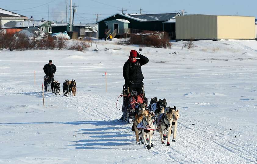 Aliy Zirkle leads Ray Redngton, Jr., out of the Koyuk checkpoint in Alaska during the Iditarod Trail