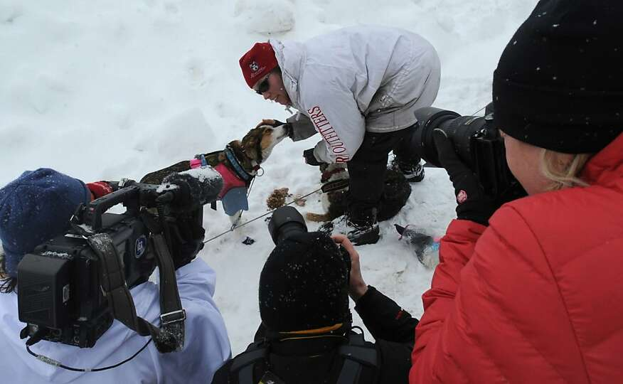 Aliy Zirkle gives an interview while taking care of her dog team in Unalakleet on Sunday, March 10,