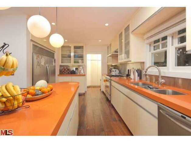Updated kitchen with bright orange counter tops.