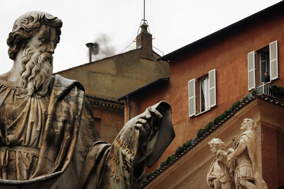 A man looks out from a window near to the statue of St Paul as black smoke billows from the chimney on the roof of the Sistine Chapel indicating that the College of Cardinals have failed to elect a new Pope on March 13, 2013 in Vatican City, Vatican. Pope Benedict XVI's successor is being chosen by the College of Cardinals in Conclave in the Sistine Chapel. The 115 cardinal-electors, meeting in strict secrecy, will need to reach a two-thirds-plus-one vote majority to elect the 266th Pontiff. Photo: Dan Kitwood, Getty Images / 2013 Getty Images
