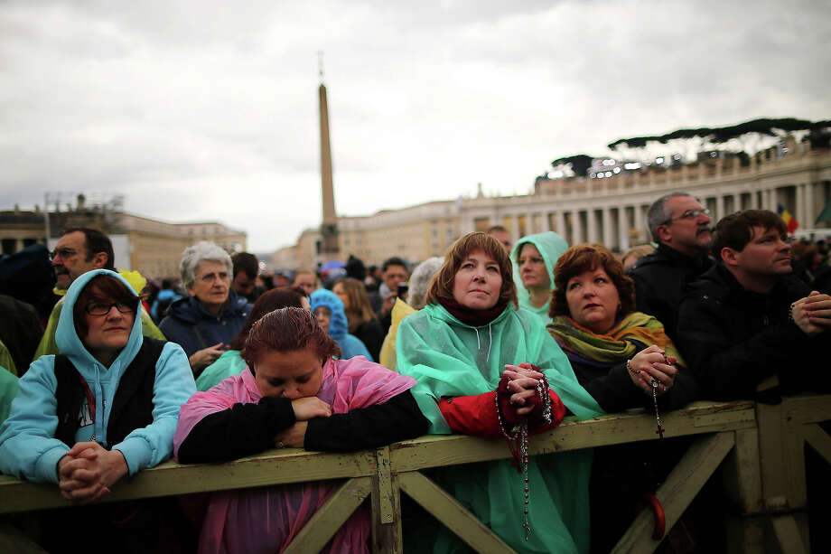 People hold rosary beads while they pray and wait for smoke to emanate from the chimney on the roof of the Sistine Chapel which will indicate whether or not the College of Cardinals have elected a new Pope on March 13, 2013 in Vatican City, Vatican. Pope Benedict XVI's successor is being chosen by the College of Cardinals in Conclave in the Sistine Chapel. The 115 cardinal-electors, meeting in strict secrecy, will need to reach a two-thirds-plus-one vote majority to elect the 266th Pontiff. Photo: Dan Kitwood, Getty Images / 2013 Getty Images