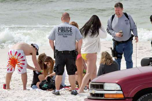 On Tuesday March 12th, 2013 officers with Florida's Division of Alcoholic Beverages and Tobacco check the IDs of spring breakers on the beach near Destin, Florida. Since Saturday, officials with the Walton County Sheriff's Office have issued more than 200 citations for underage drinking and have busted two house parties with more than 100 spring breakers. Photo: Devon Ravine, Associated Press / Northwest Florida Daily News