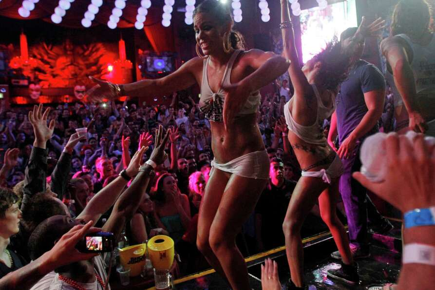 Spring Break revelers dance on a stage during a wet T-shirt contest at a nightclub in the resort cit