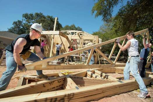 Thomas More College students, from left; Max Muckerheide, Ross Emerson and Nate Goodrich, lift a roof Wednesday, March 6, 2013 while working on a Habitat for Humanity home in Fort Walton Beach, Fla. The three are among 25 students from the Kentucky college who are spending their spring break in this northwest Florida community helping to build a house for a single mother and her child. Photo: Devon Ravine, Associated Press / Northwest Florida Daily News