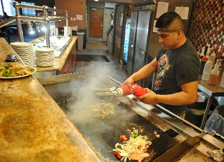 Tomas Alvarez cooks up hot dishes for guests at China Star Buffet in Beaumont. Guiseppe Barranco/cat5