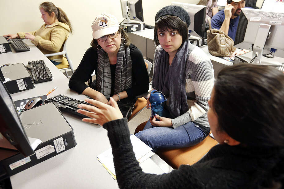 Memorial High senior Marcie Cortinas, 18, (center) and her mother Alice Chavez-Cortinas (left) get help with the Free Application for Federal Student Aid (FAFSA) from Texas A&M senior admissions counselor Jennifer Aguilar during Student Aid Saturdays at Café College. Photo: Edward A. Ornelas / San Antonio Express-News