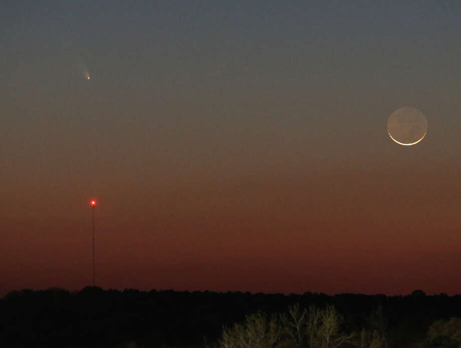 Comet Pan-STARRS is seen over the tower on the left as a one-day day waxing crescent moon is seen setting in the western sky on Tuesday, March 12, 2013.  The dark side of the moon is lit by reflected light from the Earth, and is called Earthshine.  (AP Photo/Dr. Scott M. Lieberman) Photo: Ap/getty