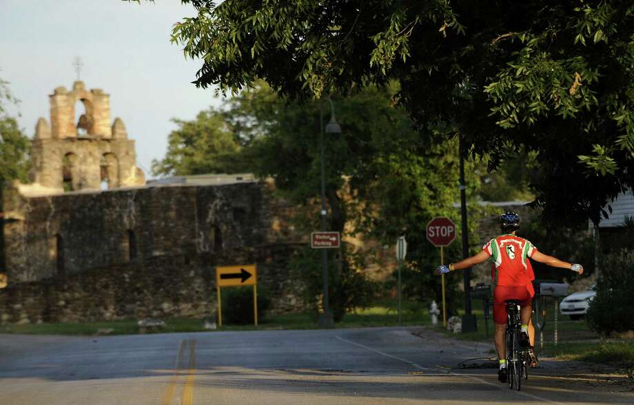 A cyclist rides by Mission Espada. U.S. Rep. Lloyd Doggett has introduced a bill to expand the boundaries for the San Antonio Missions National Historic Park. Photo: Express-News File Photo