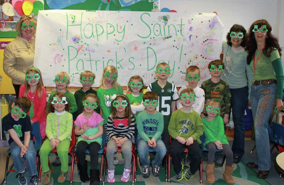 SIGN OF THE TIME Visitors to the Westport Center for Senior Activities have had a reminder this week that itís time for the weariní oí the green  with this sign made for the center by the pre-kindergarten class at St. Paul Christian School. Wearing kelly green spectacles, the sign-makers are, front row, from left: Matthew Coniglio, Eve Dolan, Lulu East, Logan Watkins, Jackson Wood, Benjamin Esser and Abigail Trooien. Back Row: Katelynn Mitchell, Seamus Brannigan, Mathew Petterson, Kate Bulkeley, Peyton Miles-Prouten, Theodore Rudolph, Blake Watkins and Gavin Villepigue. Holding the sign are school director Lesley Troup, left, and pre-kindergarten teachers Peggy Pasierb and Pilar OíConnor. Photo: Contributed Photo / Westport News