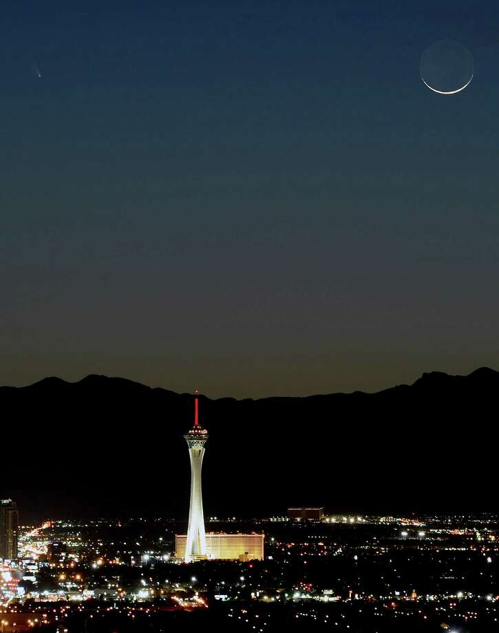 The comet PanSTARRS, above and to the left, passes over the Stratosphere Casino Hotel along with a waxing crescent moon at twilight over the Spring Mountains range on Tuesday,  March 12, 2013, in Las Vegas, Nev.   (Photo by Ethan Miller/Getty Images) Photo: Ethan Miller, Ap/getty / 2013 Getty Images