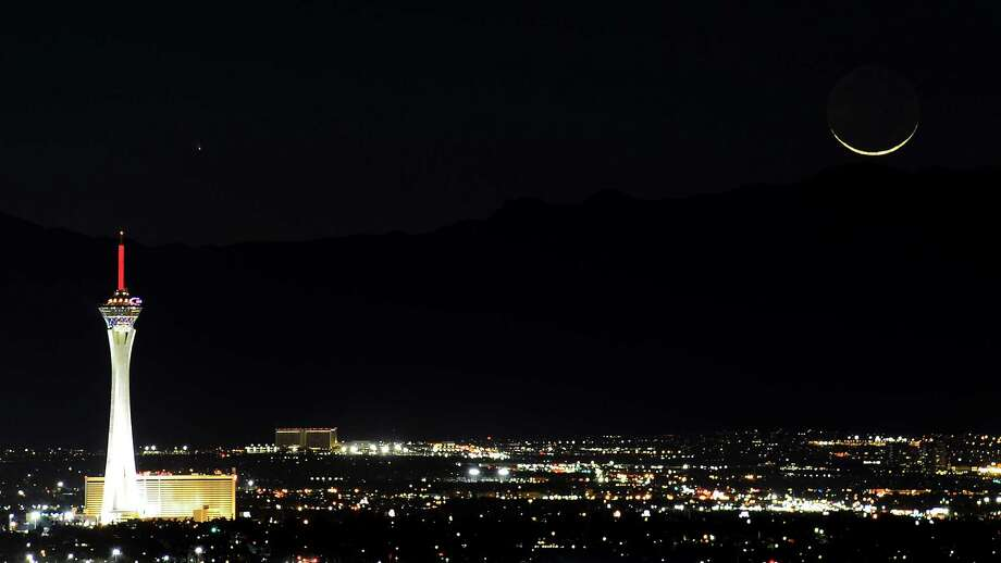 The comet PanSTARRS, above and to the right, passes over the Stratosphere Casino Hotel along with a waxing crescent moon over the Spring Mountains range on Tuesday, March 12, 2013, in Las Vegas, Nev. (Photo by Ethan Miller/Getty Images) Photo: Ethan Miller, Ap/getty / 2013 Getty Images