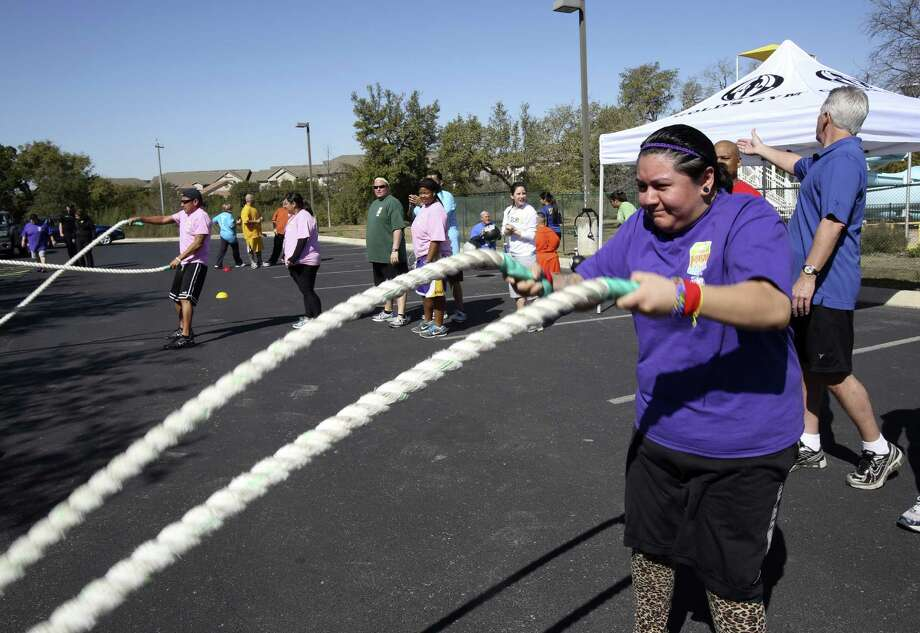 San Antonian Ashley Gonzales works with battling ropes during a workout with H-E-B Slim Down Showdown. She's learned that taking bike rides helps combat stress. Photo: Photos By Helen L. Montoya / Conexión