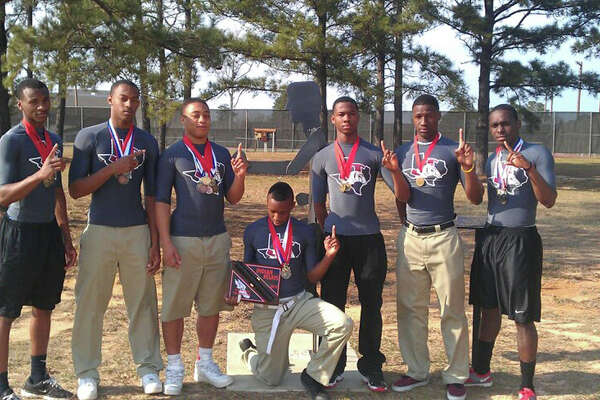 Josh Thomas, Chris Fowler, Donovan Middleton, LeDale White, Daniel Adams, Jonavon Limbrick, and Kendall Shankle.  Several members of the track team pose with the Indian Relays Championship Trophy infront of the late Coach Lloyd Weatherspoon memorial at the JHS practice track.