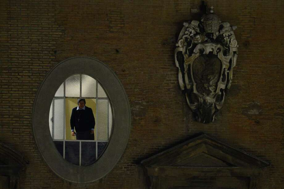 A nun stands at a window at St Peter's square after white smoke billowed from the chimney of the Sistine Chapel announcing that Catholic Church cardinals had elected a new pope during a conclave on March 13, 2013 at the Vatican. Photo: AFP, AFP/Getty / 2013 AFP