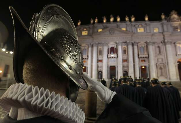A Swiss guard salutes, in St. Peter's Square at the Vatican, Wednesday, March 13, 2013. The Catholic church has chosen a new pope. White smoke is billowing from the chimney of the Sistine Chapel, meaning 115 cardinals in a papal conclave have elected a new leader for the world's 1.2 billion Catholics. (AP Photo/Gregorio Borgia) Photo: Gregorio Borgia, Associated Press