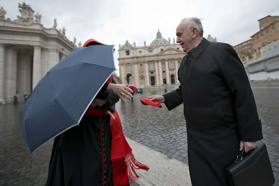 Argentine Cardinal Jorge Mario Bergoglio, right, hands Canadian Cardinal Marc Ouellet his skull cap after the wind blew it off as they walk in St. Peter's Square after attending a cardinals' meeting, at the Vatican, Wednesday, March 6, 2013. Cardinals are meeting to discuss the problems of the church and to get to know one another because there is no clear front-runner in the election of the new pope. Photo: Andrew Medichini, Associated Press