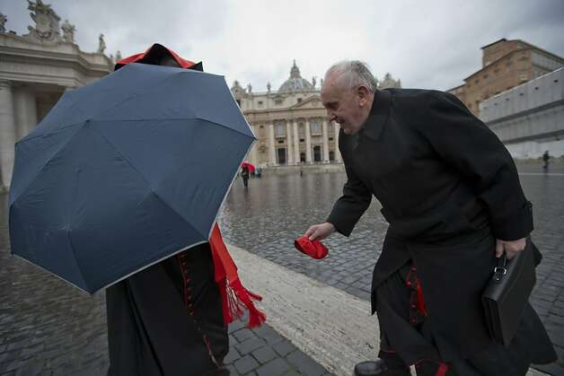 Argentine Cardinal Jorge Mario Bergoglio, right, picks up Canadian Cardinal Marc Ouellet's skull cap after the wind blew it off as they walk in St. Peter's Square after attending a cardinals' meeting, at the Vatican, Wednesday, March 6, 2013. Cardinals are meeting to discuss the problems of the church and to get to know one another because there is no clear front-runner in the election of the new pope. Photo: Andrew Medichini, Associated Press