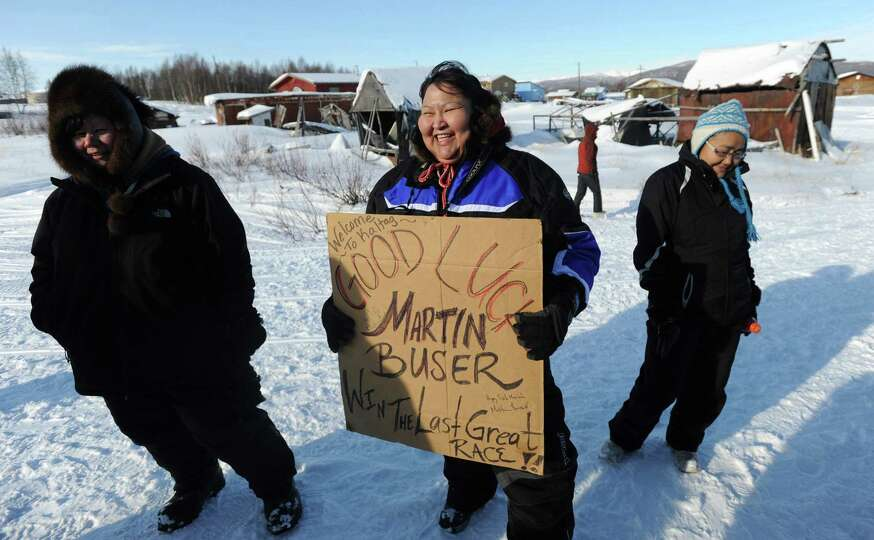 Ann Neglaska of Kaltag, Alaska, holds a sign that four-time Iditarod champion Martin Buser signed th