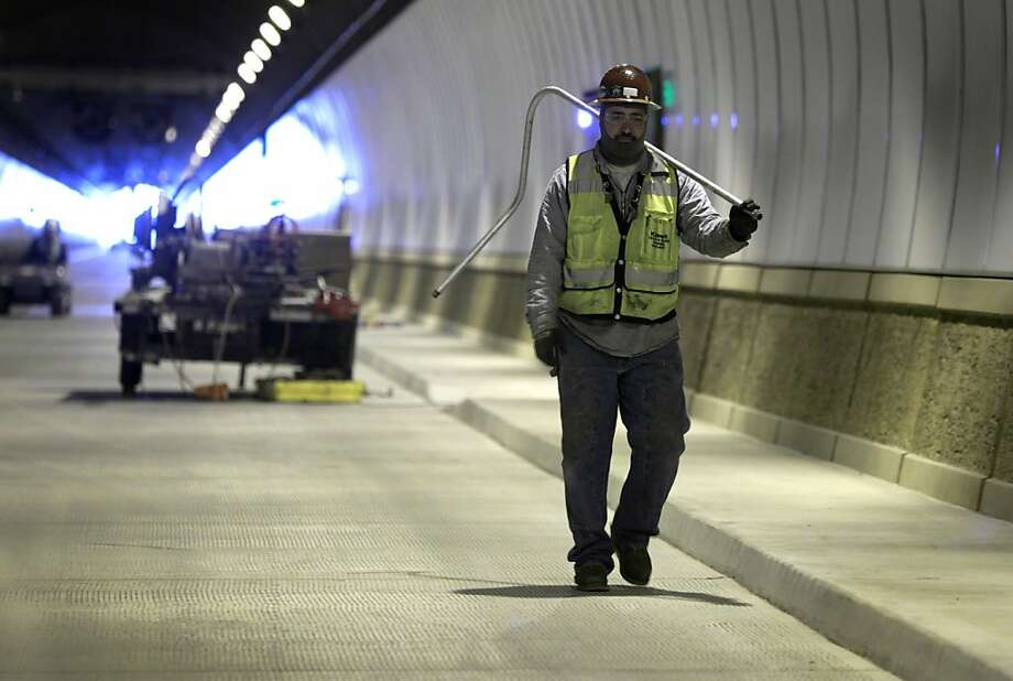 Alex Lopes carries electrical conduit through the tunnel's northbound bore in December. Photo: Paul Chinn, The Chronicle