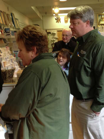 Employees and shoppers at O'Connor Church Goods in Latham react with excitement as they  watch the announcement of th new pope on a computer screen on Wednesday, March 13, 2013, afternoon. (Paul Grondahl / Times Union)
