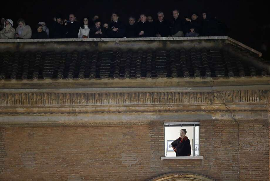 VATICAN CITY, VATICAN - MARCH 13:  A woman peers out of a window as others look on from a rooftop above while newly elected Pope Francis I appears on the central balcony of St Peter's Basilica on March 13, 2013 in Vatican City, Vatican.  Argentinian Cardinal Jorge Mario Bergoglio was elected as the 266th Pontiff and will lead the world's 1.2 billion Catholics.  (Photo by Joe Raedle/Getty Images) Photo: Joe Raedle, Getty Images