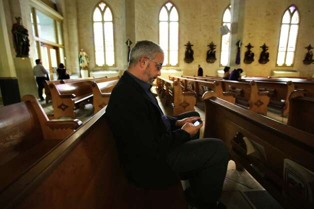 Kevin McManus checks his smart phone, as he sits in a pew in San Fernando Cathedral, for the announcement of the new Pope in the Vatican, on Wednesday, March 13, 2013, at San Fernando Cathedral. McManus is catholic and is interested in who the next Pope will be. Photo: Bob Owen, San Antonio Express-News / ©2013 San Antonio Express-News