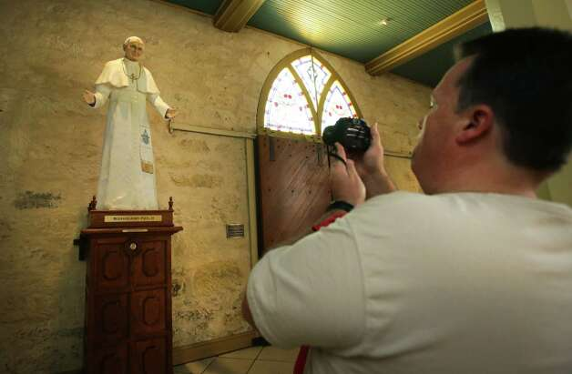 "Rene Zimmermann of Houston, stops to take a picture of a statue of Pope John Paul II in San Fernando Cathedral, who visited the Alamo city in 1987.  Zimmermann, a catholic, said, ""it doesn't matter where he's from, but wheather or not they can lead the church"", of the announcement of the new Pope in the Vatican, on Wednesday, March 13, 2013. Photo: Bob Owen, San Antonio Express-News / ©2013 San Antonio Express-News"