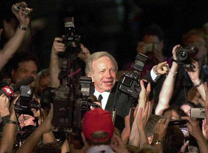 Vice presidential candidate Joe Lieberman is swarmed by photographers as he enters the Democratic National Convention in the Staples Center Tuesday, Aug. 15, 2000, in Los Angeles. (AP Photo/Ron Edmonds)