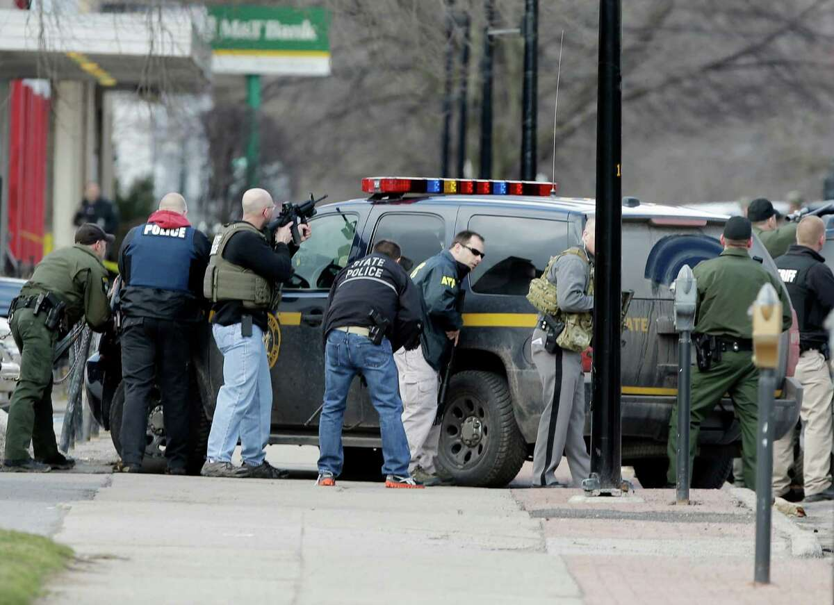 Law enforcement officers take cover along Main Street in Herkimer, N.Y., when shots were fired while they were searching for a suspect in two shootings that killed four and injured at least two on, Wednesday, March 13, 2013. Authorities were looking for 64-year-old Kurt Meyers, said Herkimer Police Chief Joseph Malone. Officials say guns and ammunition were found inside his Mohawk apartment after emergency crews were sent to a fire there Wednesday morning. (AP Photo/Mike Groll)