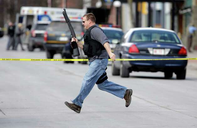 Law enforcement officers run for cover along Main Street  in Herkimer, N.Y., when shots were fired while they were searching for a suspect in two shootings that killed four and injured at least two on, Wednesday, March 13, 2013. Authorities were looking for 64-year-old Kurt Meyers, said Herkimer Police Chief Joseph Malone. Officials say guns and ammunition were found inside his Mohawk apartment after emergency crews were sent to a fire there Wednesday morning.  (AP Photo/Mike Groll) Photo: Mike Groll