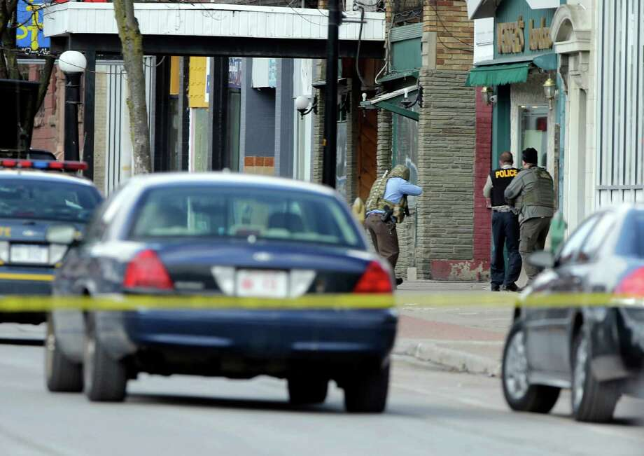 Law enforcement officers take cover along Main Street when shots were fired while they were searching for a suspect in two shootings that killed four and injured at least  two on, Wednesday, March 13, 2013, in Herkimer, N.Y. Authorities were looking for 64-year-old Kurt Meyers, said Herkimer Police Chief Joseph Malone. Officials say guns and ammunition were found inside his Mohawk apartment after emergency crews were sent to a fire there Wednesday morning.  (AP Photo/Mike Groll) Photo: Mike Groll
