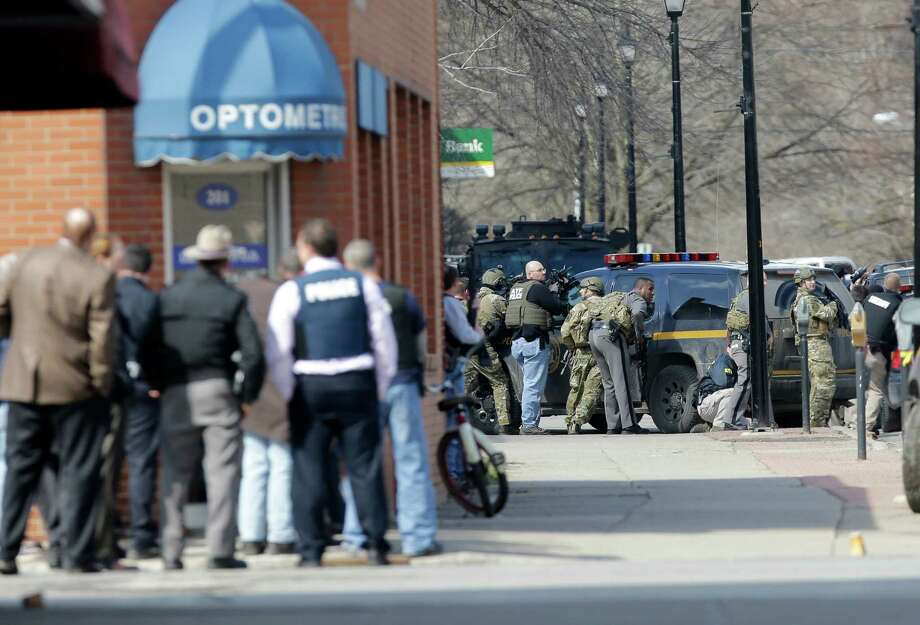 Law enforcement officers take cover along Main Street when shots were fired while searching for a suspect in two shootings that killed four and injured at least two on Wednesday, March 13, 2013, in Herkimer, N.Y. Authorities were looking for 64-year-old Kurt Meyers, said Herkimer Police Chief Joseph Malone. Officials say guns and ammunition were found inside his Mohawk apartment after emergency crews were sent to a fire there Wednesday morning.  (AP Photo/Mike Groll) Photo: Mike Groll