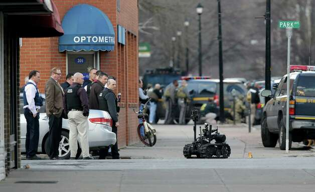 A police robot moves along the street while police search for a suspect in two shootings that killed four and injured at least  two on, Wednesday, March 13, 2013, in Herkimer, N.Y. Multiple gunshots rang out as police on foot and in a helicopter swarmed two upstate New York villages in search of a 64-year-old man they say opened fire at a car wash and a barbershop Wednesday morning, killing four people and wounding at least two others.  (AP Photo/Mike Groll) Photo: Mike Groll