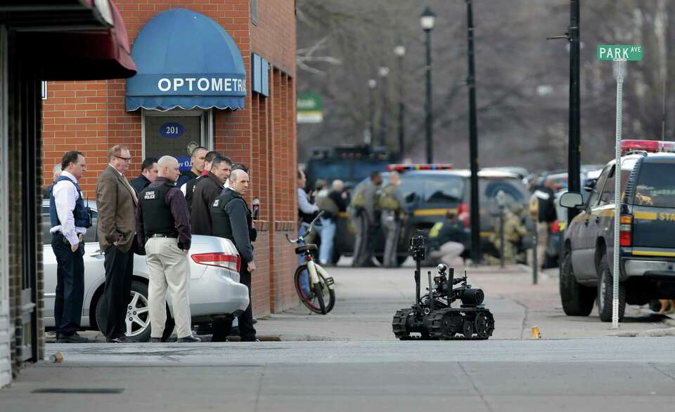A police robot moves along the street while police search for a suspect in two shootings that killed