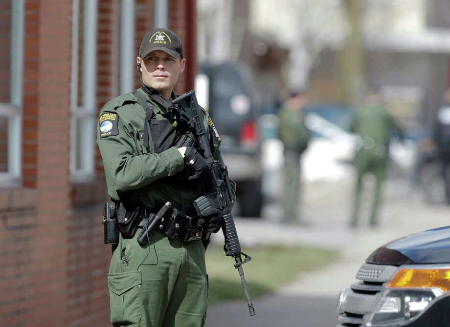 A law enforcement officer stands on Main Street in Herkimer, N.Y., during the search for a suspect in two shootings that killed four and injured at least  two on, Wednesday, March 13, 2013. Authorities were looking for 64-year-old Kurt Meyers, said Herkimer Police Chief Joseph Malone. Officials say guns and ammunition were found inside his Mohawk apartment after emergency crews were sent to a fire there Wednesday morning.  (AP Photo/Mike Groll) Photo: Mike Groll