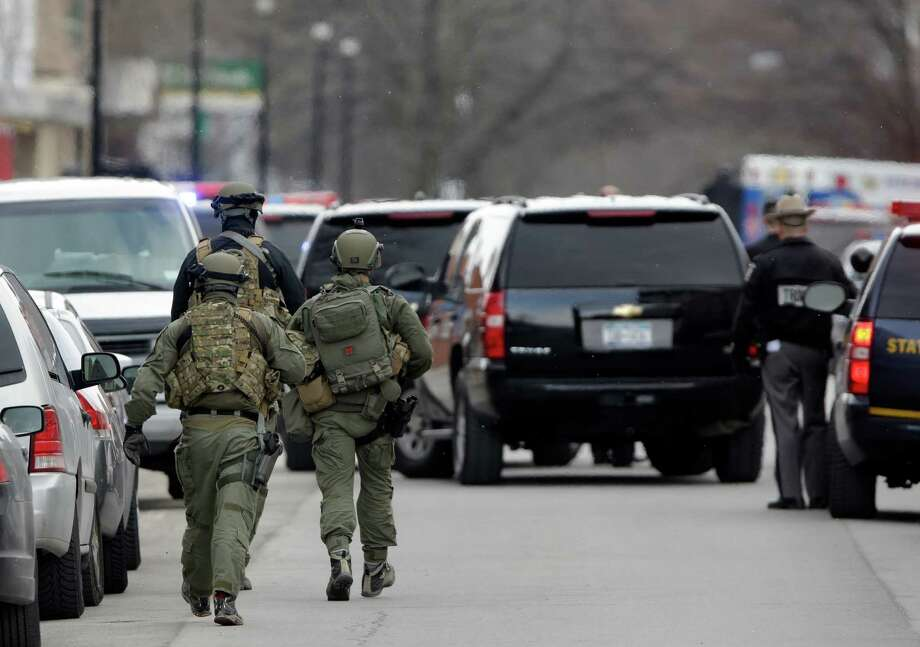 Police walk along Main Street in Herkimer, N.Y., as they search for a suspect in two shootings that killed four and injured at least two on, Wednesday,  March 13, 2013. Multiple gunshots rang out as police on foot and in a helicopter swarmed two upstate New York villages in search of a 64-year-old man they say opened fire at a car wash and a barbershop Wednesday morning, killing four people and wounding at least two others.  (AP Photo/Mike Groll) Photo: Mike Groll