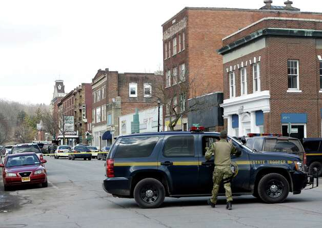Law enforcement officers block off Main Street  in Herkimer, N.Y., while searching for a suspect in two shootings that killed four and injured at least  two on, Wednesday, March 13, 2013. Authorities were looking for 64-year-old Kurt Meyers, said Herkimer Police Chief Joseph Malone. Officials say guns and ammunition were found inside his Mohawk apartment after emergency crews were sent to a fire there Wednesday morning.  (AP Photo/Mike Groll) Photo: Mike Groll