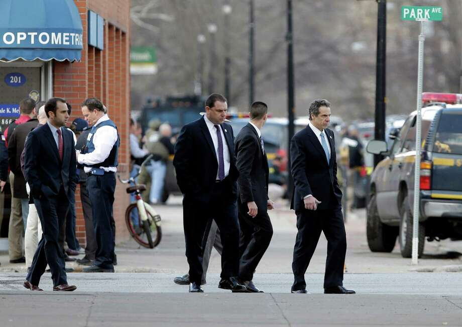 New York Gov. Andrew Cuomo, right, walks to a vehicle as law enforcement officers take cover along Main Street after shots were fired while they were searching for a suspect in two shootings that killed four and injured at least  two on, Wednesday, March 13, 2013, in Herkimer, N.Y. Authorities were looking for 64-year-old Kurt Meyers, said Herkimer Police Chief Joseph Malone. Officials say guns and ammunition were found inside his Mohawk apartment after emergency crews were sent to a fire there Wednesday morning.  (AP Photo/Mike Groll) Photo: Mike Groll