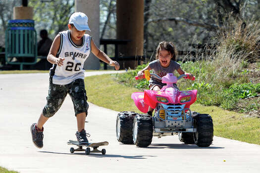 Jacob Garza (7, left) and his sister Jazlyn Garza (5) enjoy the day on their rides at Padre County Park on the Mission Reach on Wednesday, March 13, 2013.  MARVIN PFEIFFER/ mpfeiffer@express-news.net Photo: MARVIN PFEIFFER, Marvin Pfeiffer/ Express-News / Express-News 2013