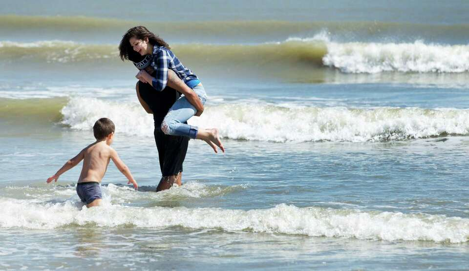 Julia Orellana, of Killeen, laughs as she is carried into the surf by her boyfriend, Chrstian Orta,