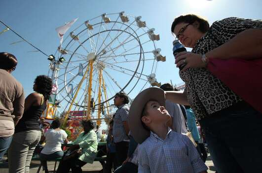 Jack Rumfield, 4, turns to his mother Michele Rumfield who patiently wait in line to purchase tickets for carnival rides during the Spring Break Stampede at Houston Livestock Show and Rodeo on Wednesday, March 13, 2013, in Houston. Photo: Mayra Beltran, Houston Chronicle / © 2013 Houston Chronicle
