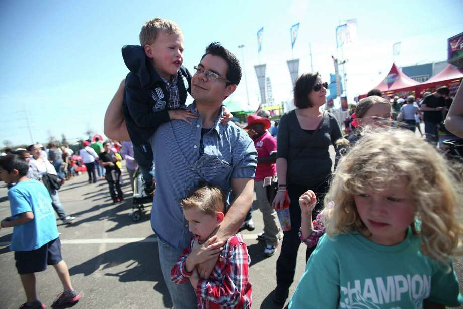 Oscar Castiblanco carries son Michael Nichols, 3, and holds Matthew Nichols, 6, while Hayley Nichols, 7, and the rest of the family wait in a long line for the super slide during the Spring Break Stampede at the Houston Livestock Show and Rodeo on Wednesday, March 13, 2013, in Houston. Photo: Mayra Beltran, Houston Chronicle / © 2013 Houston Chronicle