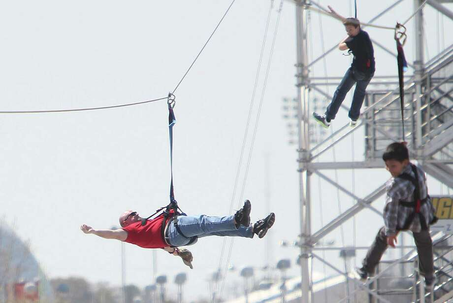 Lee Millis joins his son on the zip line with many others attending the Spring Break Stampede during the Houston Livestock Show and Rodeo at Reliant Park on Wednesday, March 13, 2013, in Houston. Photo: Mayra Beltran, Houston Chronicle / © 2013 Houston Chronicle