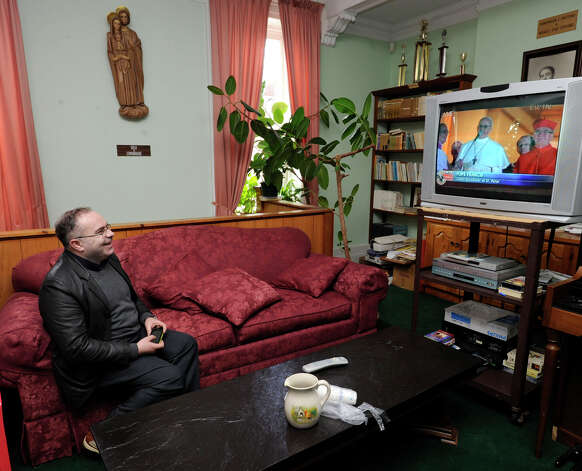 Father Jose Martins, pastor of the Immaculate Heart of Mary Parish on Deer Hill Avenue in Danbury, watches as the new pope is introduced to the world, Wednesday, March 13, 2013. Photo: Carol Kaliff / The News-Times