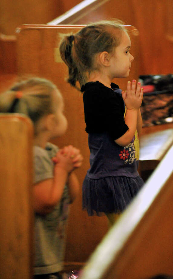 Three-year-old Savannah Murray, left, walks with her sister, Alexis, 4, down the aisle before receiving communion during afternoon mass at Sacred Heart Church in Stamford on Wednesday, March 13, 2013. Today, Argentine Cardinal Jorge Mario Bergoglio was elected pope, taking the name Pope Francis I. Photo: Jason Rearick / The Advocate