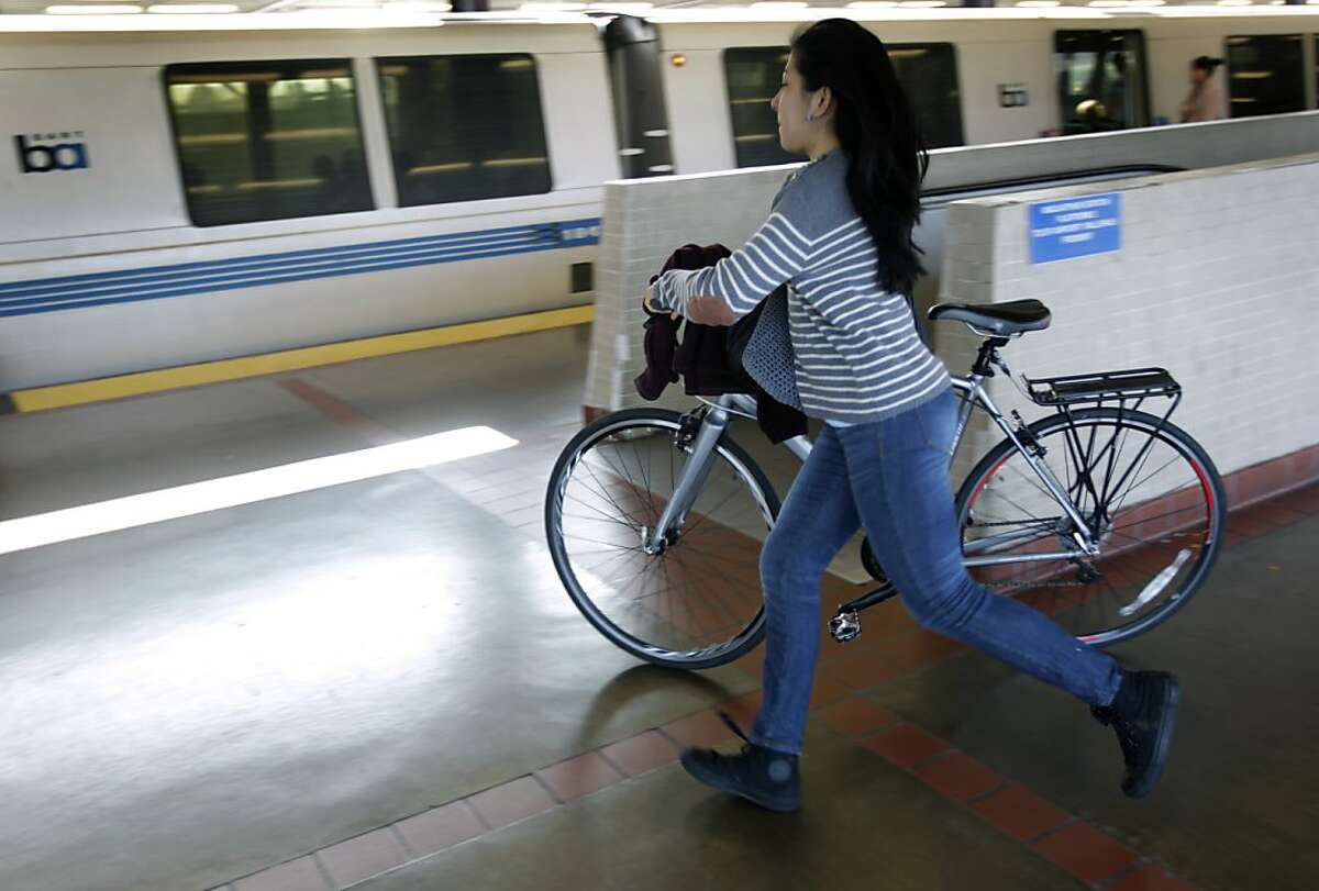 A bicycle commuter makes her connection to a San Francisco-bound train at the MacArthur BART station.