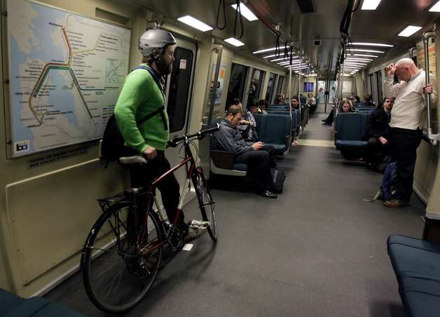 Nicholas Price rides BART with his bicycle from San Francisco to the West Oakland Station. The transit agency usually lets bikes on board trains during nonpeak hours, but will try all-day access next week. Photo: Paul Chinn, The Chronicle