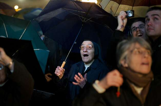 A nun reacts after white smoke billowed from the chimney on the Sistine Chapel indicating that a new pope has been elected in St. Peter's Square at the Vatican, Wednesday, March 13, 2013. Argentine Cardinal Jorge Bergoglio, who chose the name of Pope Francis, is the 266th pontiff of the Roman Catholic Church. (AP Photo/Emilio Morenatti) Photo: Emilio Morenatti, Associated Press