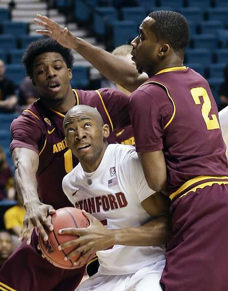 Stanford's Chasson Randle, center, is double teamed under the basket by Arizona State's Carrick Feli
